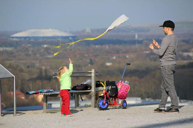 Ein Kind lässt einen Drachen steigen. Im Hintergrund die Arena auf Schalke