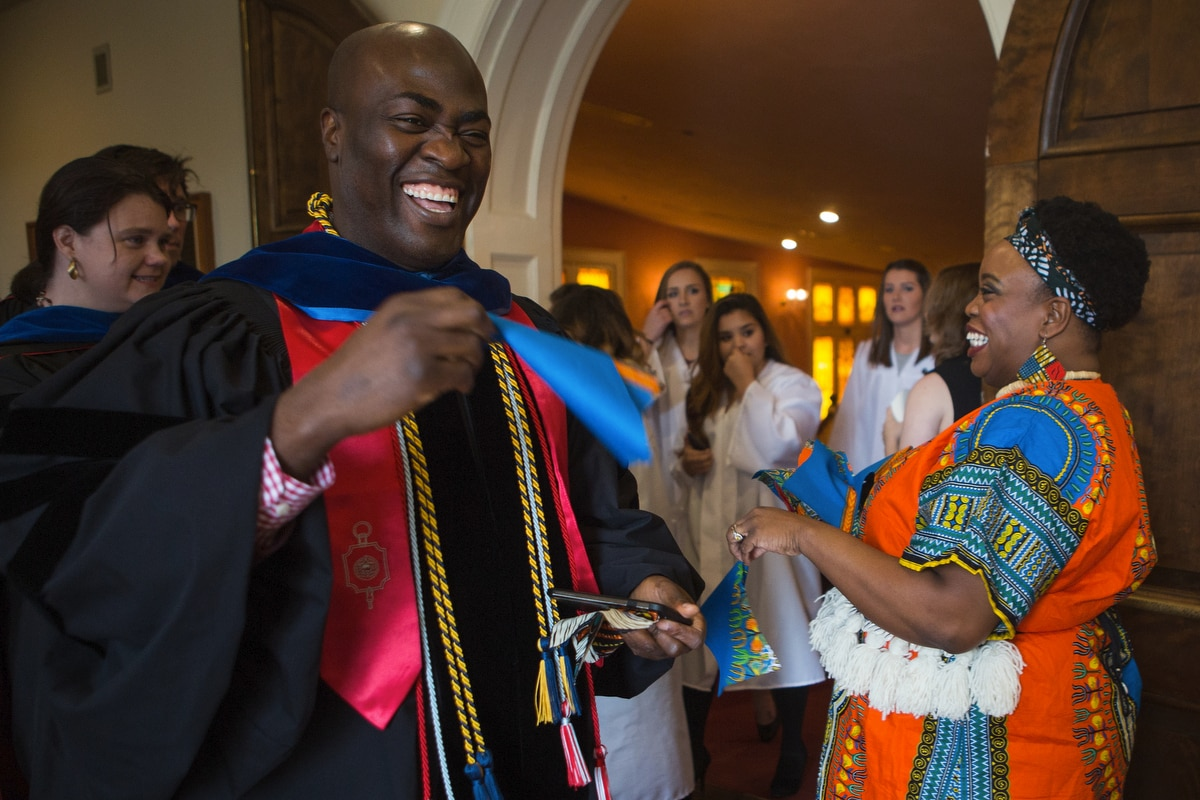Gnimbin Ouattara, associate professor of history, reacts after receiving an African Print Wax cloth from Madia Cooper-Ashirifi, visiting assistanmt professor of dance, for a celebratory dance during the Martin Luther King Jr. Day Convocation.