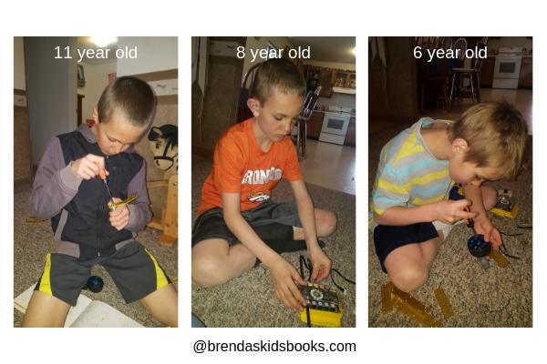 11 year old boy, 8 year old boy, 6 year old boy putting together the Tenergy Robot