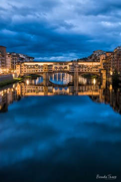 Italy, Florence. Dusk falls on the Arno River and the Ponte Vecchio bridge.