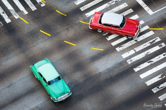 Two cars moving through an intersection.