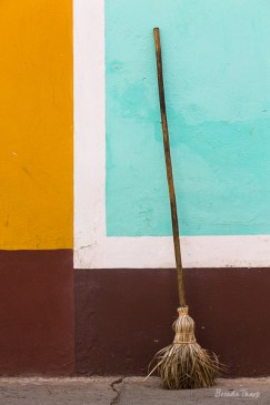 A broom leans against colorful walls.
