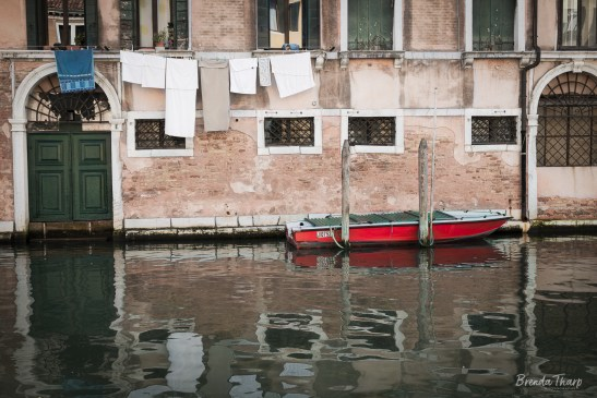 Red boat, canal and laundry in Venice, Italy.