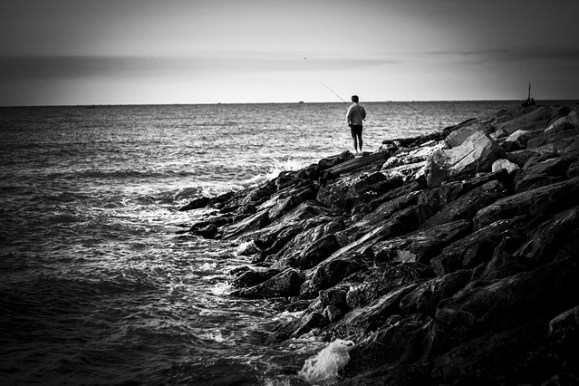 Man overlooking the ocean from a rocky coastline