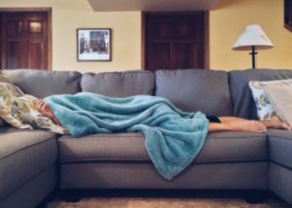 Person asleep on the couch under a blanket