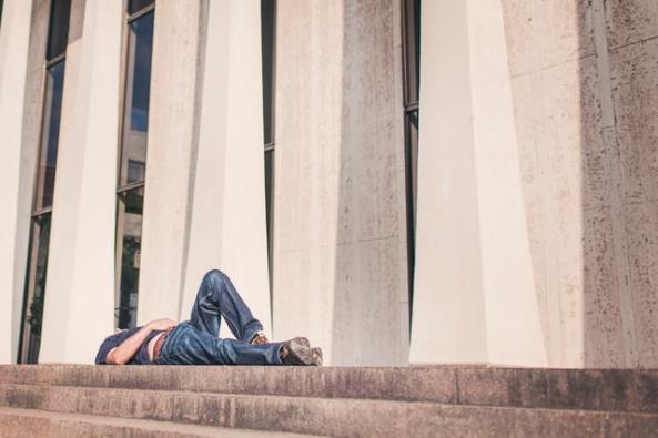 Lazy man sleeping on building steps