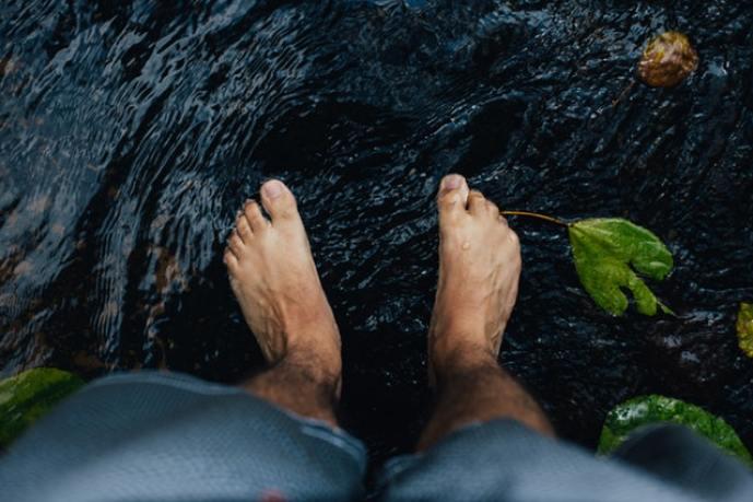 A man staring down at his bare feet