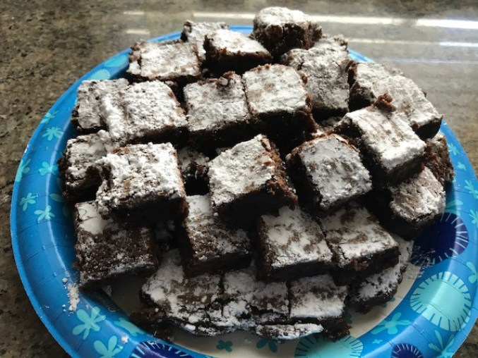 A plate of brownies topped with powdered sugar