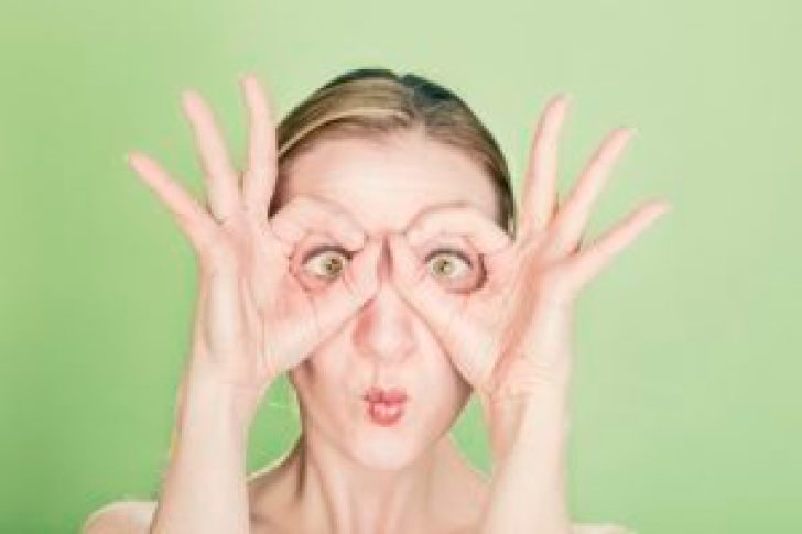 Woman using her hands to mimic a pair of glasses
