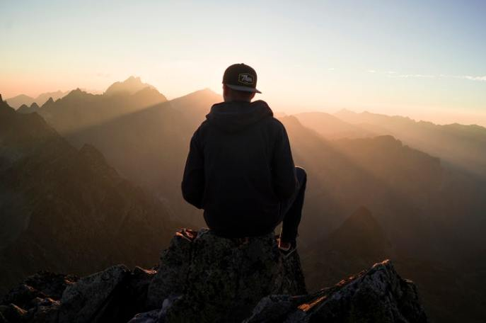 Man sitting on top of a mountain at sunset