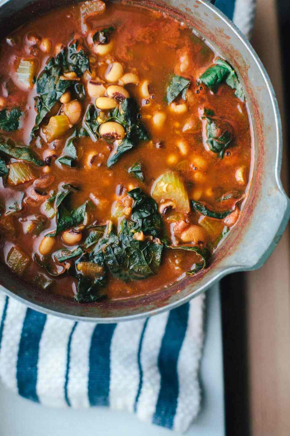 A Big Pot of Meatless Black Eyed Pea Soup with Kale and Black Eyed Peas Peaking Out of a Red Broth.