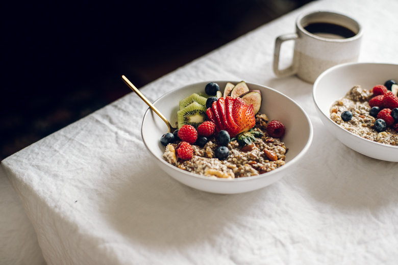 a bowl of porridge on a table, topped with fruit, and a cup of coffee in the background