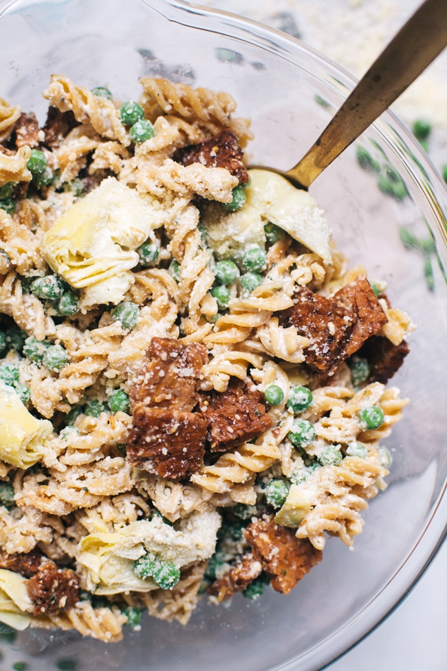 Healthy Spring Pasta Salad with artichoke hearts, spring peas, smokey tempeh, tzatziki, and parmesan!
