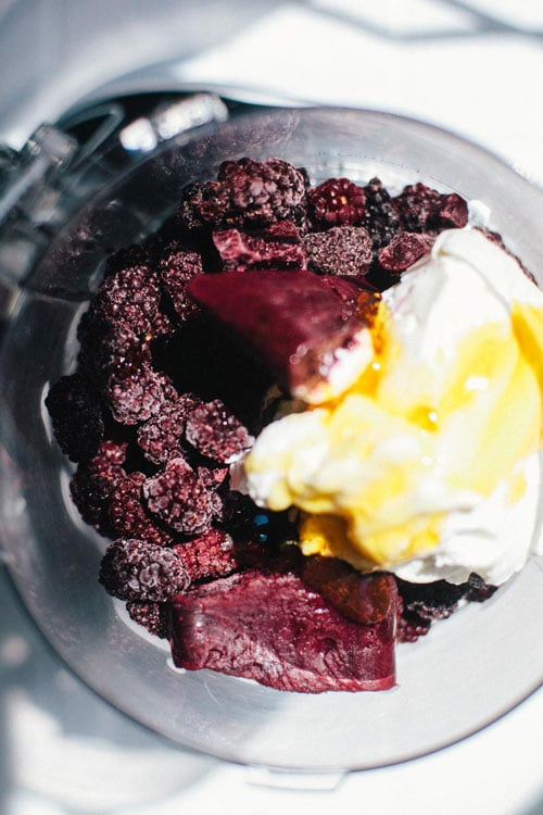 a food processor filled with blackberries, frozen acai, greek yogurt and honey