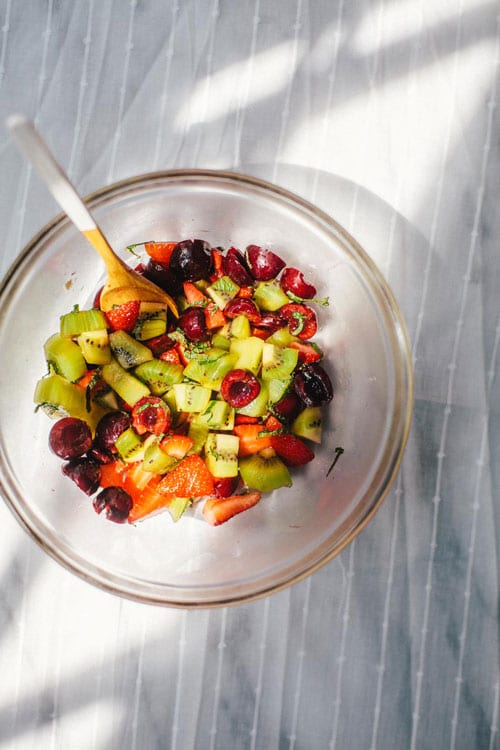 A clear bowl of chopped strawberries, kiwi, and cherries glistening in the light of a window
