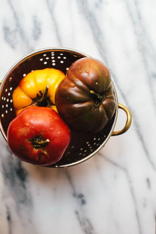 three heirloom tomatoes sitting in a small copper colander on top of a marble background