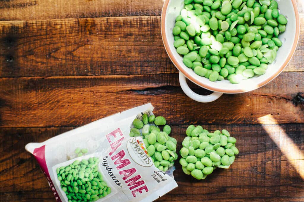 A colander of steamed edamame, plus a bag of frozen edamame from Sprouts Farmers Market.