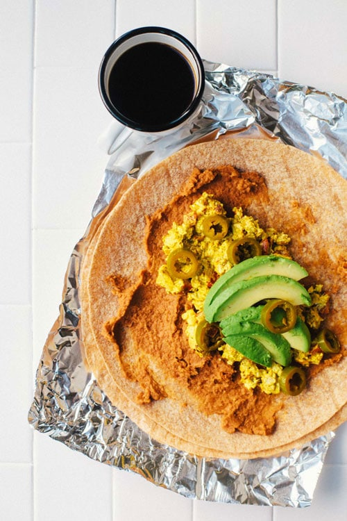 An open face breakfast burrito with refried beans, tofu scramble, avocado slices, and pickled jalapenos on top.