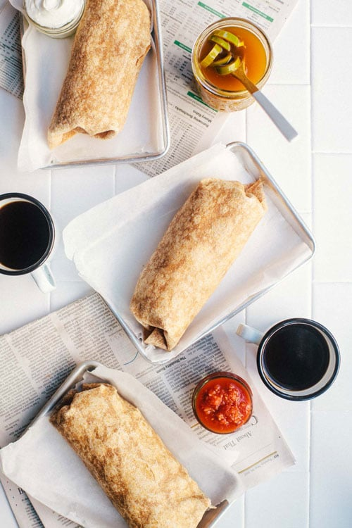 Three rolled breakfast burritos on trays with coffee, salsa, and pickled jalapenos surrounding them.