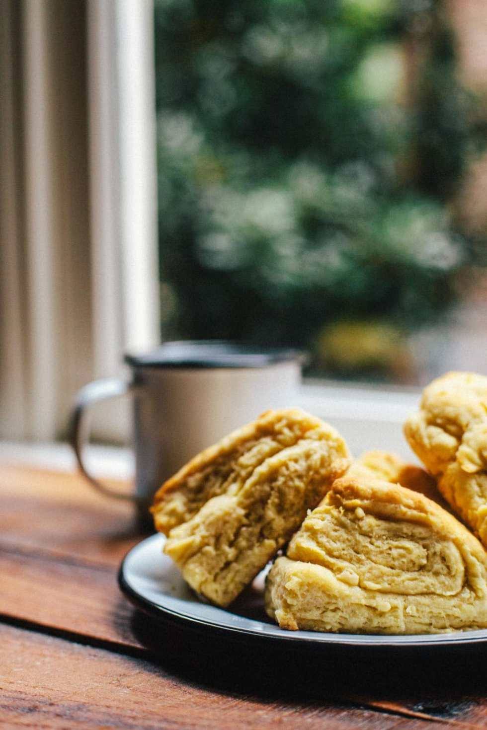 A side view of three fluffy, flaky buttermilk biscuits with coffee and a window in the background