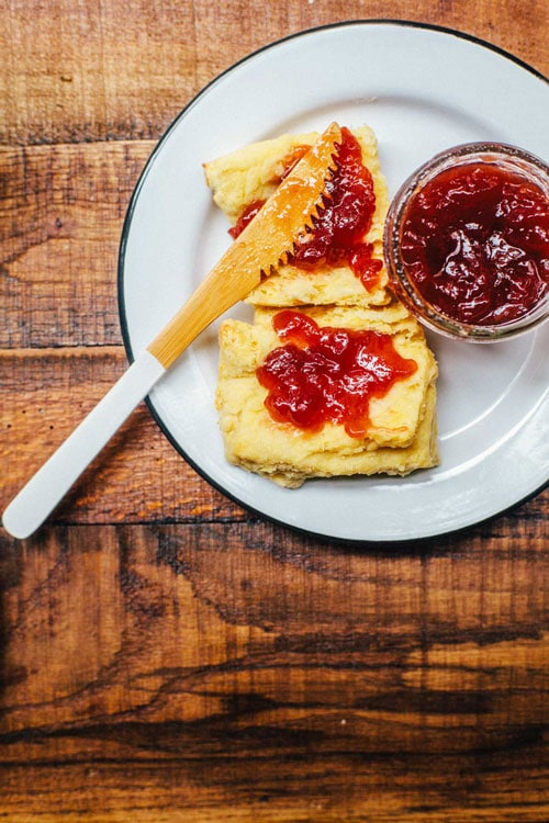 A white plate with a fluffy southern biscuit cut in half and slathered with strawberry jam