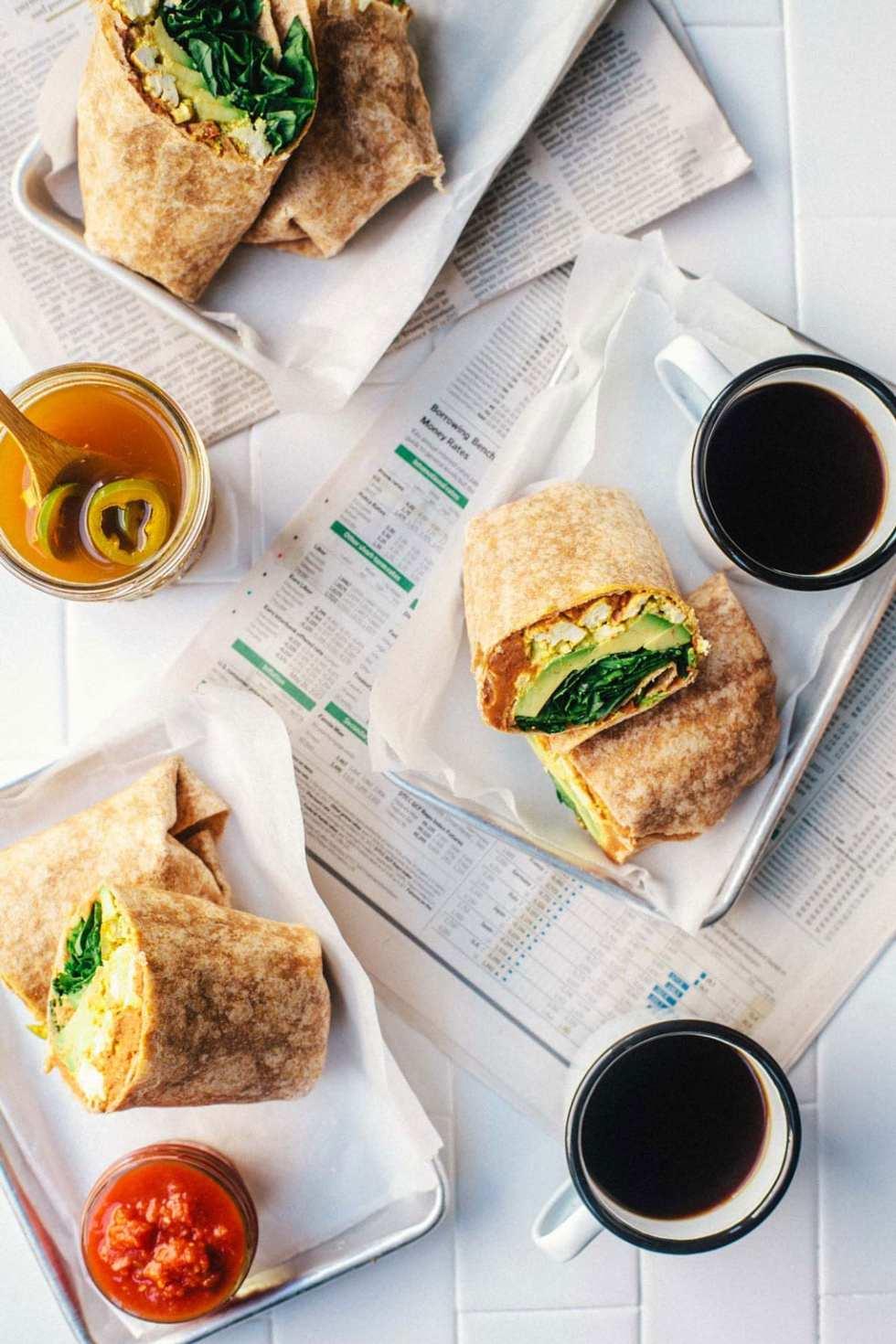 Three trays of vegan breakfast burritos, each one cut in half revealing the tofu scramble inside!