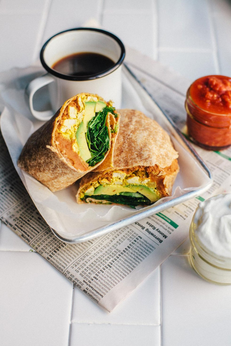 An vegan tofu scramble breakfast burrito cut in half on a small tray with a cup of coffee.