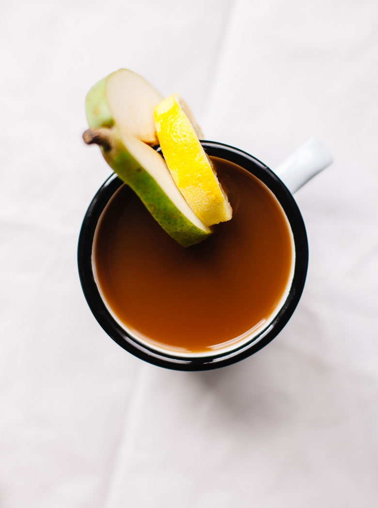 a cup of pear mint juice with a pear and lemon slice on the mug
