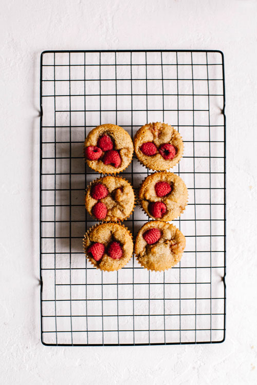 six raspberry rose muffins on a cooling rack