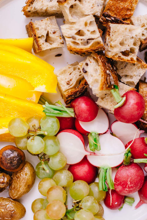 radishes, grapes, yellow bell peppers, bread, and baby potatoes