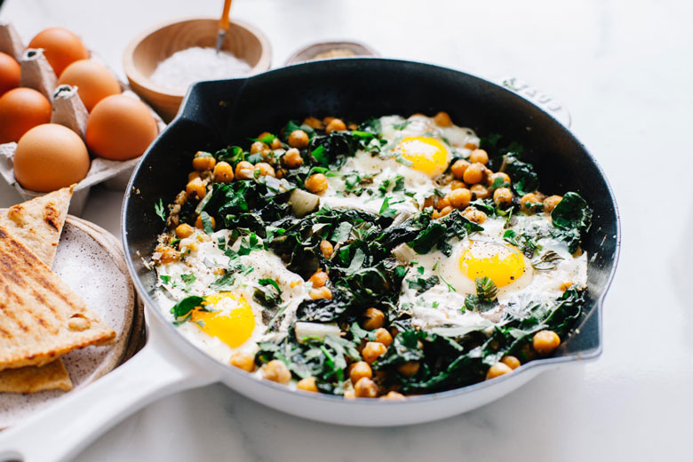 large cast iron skillet with eggs, chickpeas, swiss chard and yogurt