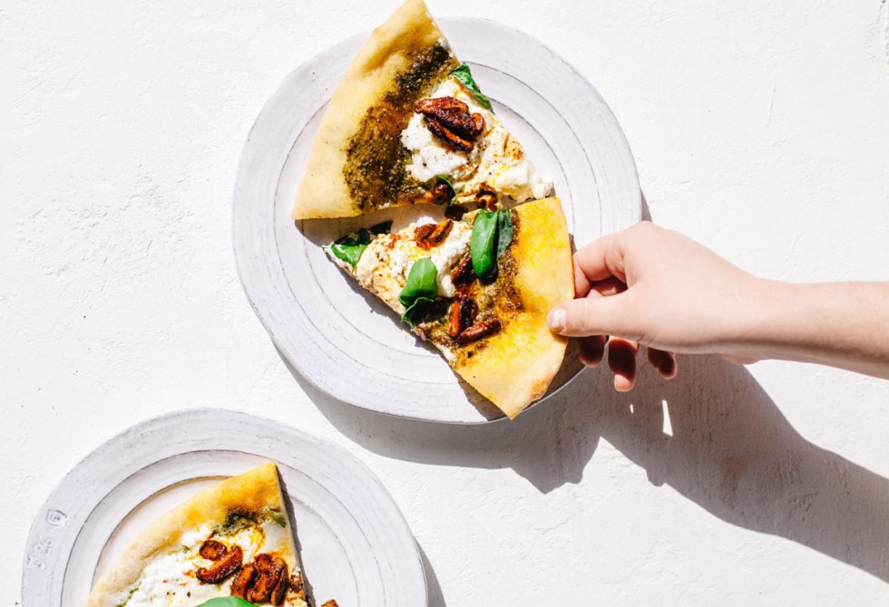 A hand reaching for a slice of Marinated Mushroom Pesto Pizza
