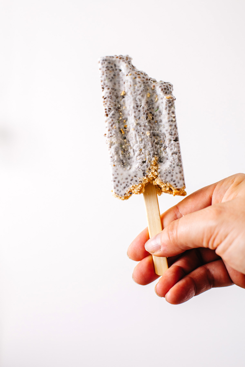 hand holding a chia pudding popsicle with a bite taken out of it