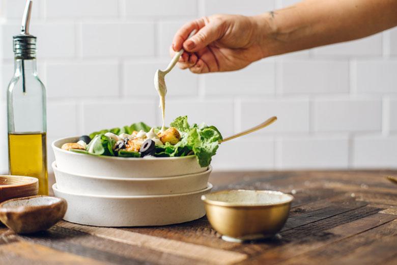 pouring tofu caesar dressing on salad