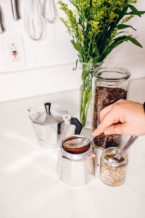 tamping coffee grounds with a spoon