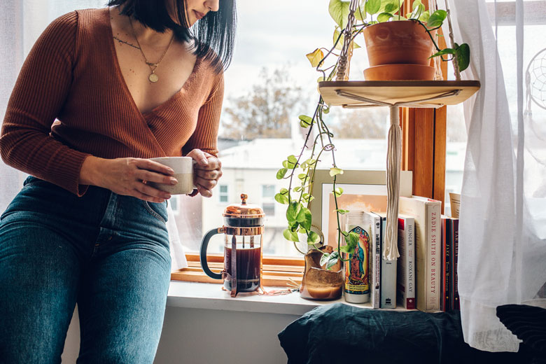 girl with french press in window