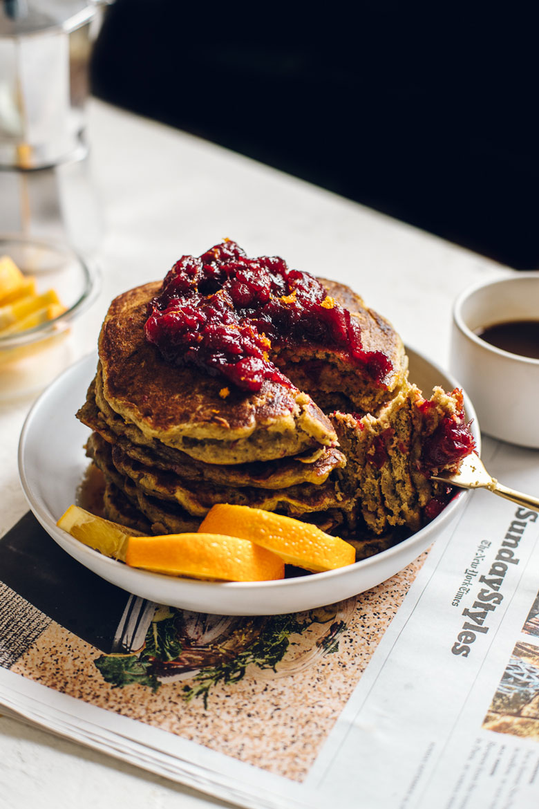 a stack of pancakes topped with cranberry sauce and maple syrup