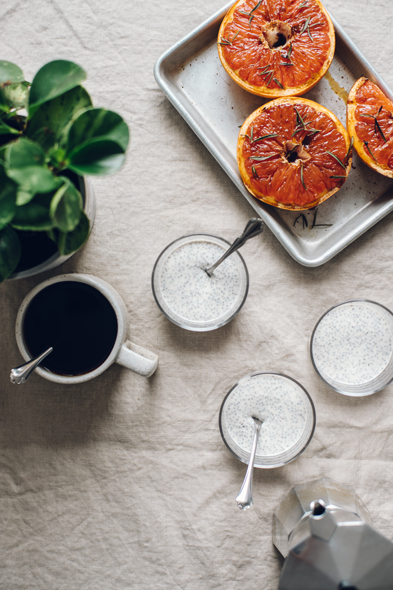 Three small bowls of greek yogurt chia pudding, a tray of roasted grapefruit, coffee, and a plant