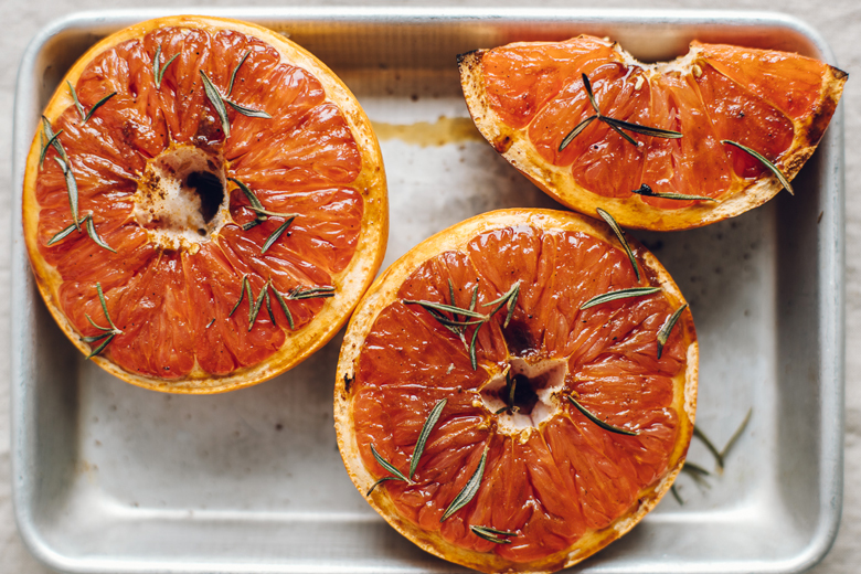 overhead of a tray of roasted grapefruit topped with rosemary sprigs