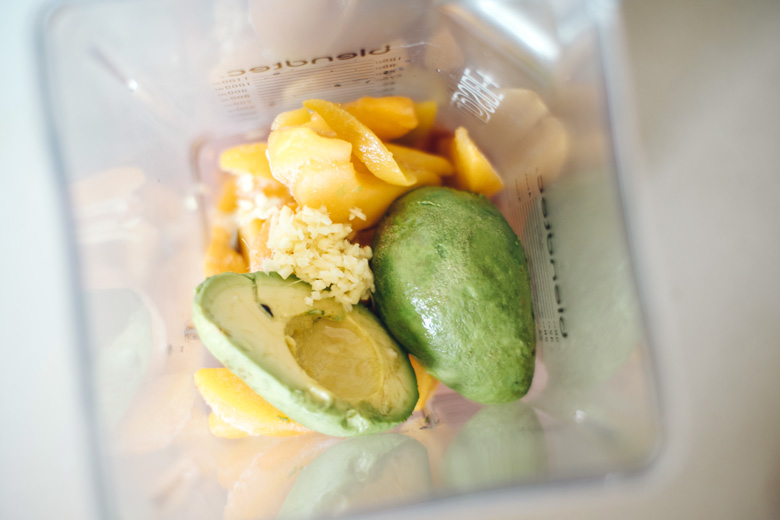 frozen peach, avocado, ginger, and coconut water in a blender