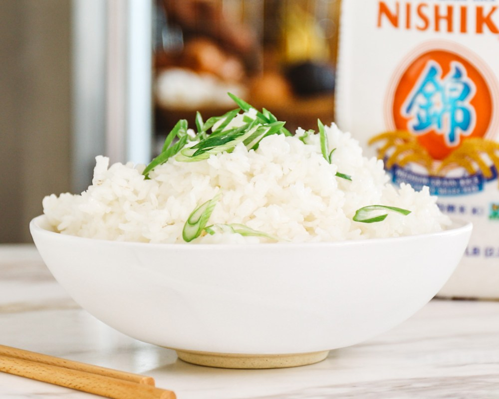 a bowl of sushi rice on a counter with scallions on top