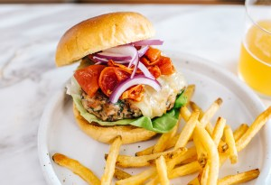A roasted tomato turkey burger on a plate with french fries