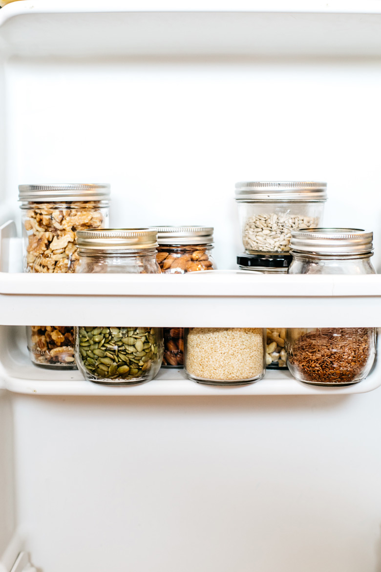 nuts and seeds in jars inside a refrigerator door