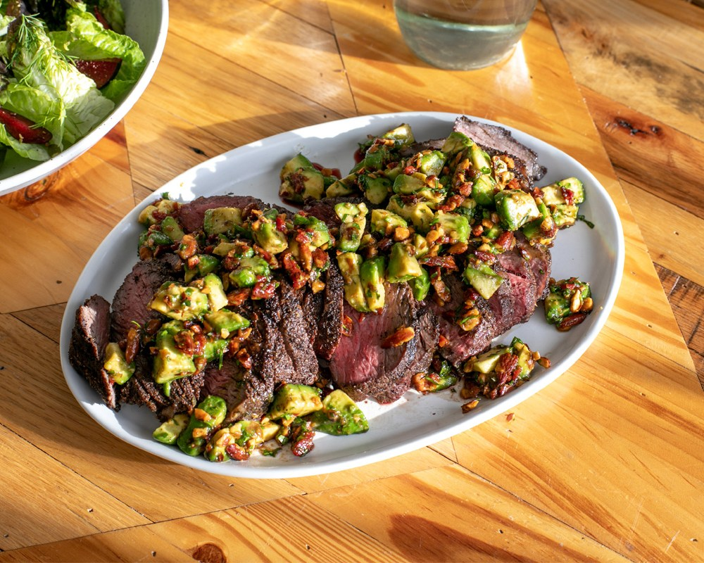 a side angle view of an oval plate with sliced steak and avocado relish on it, sitting on a wooden table in direct sunlight