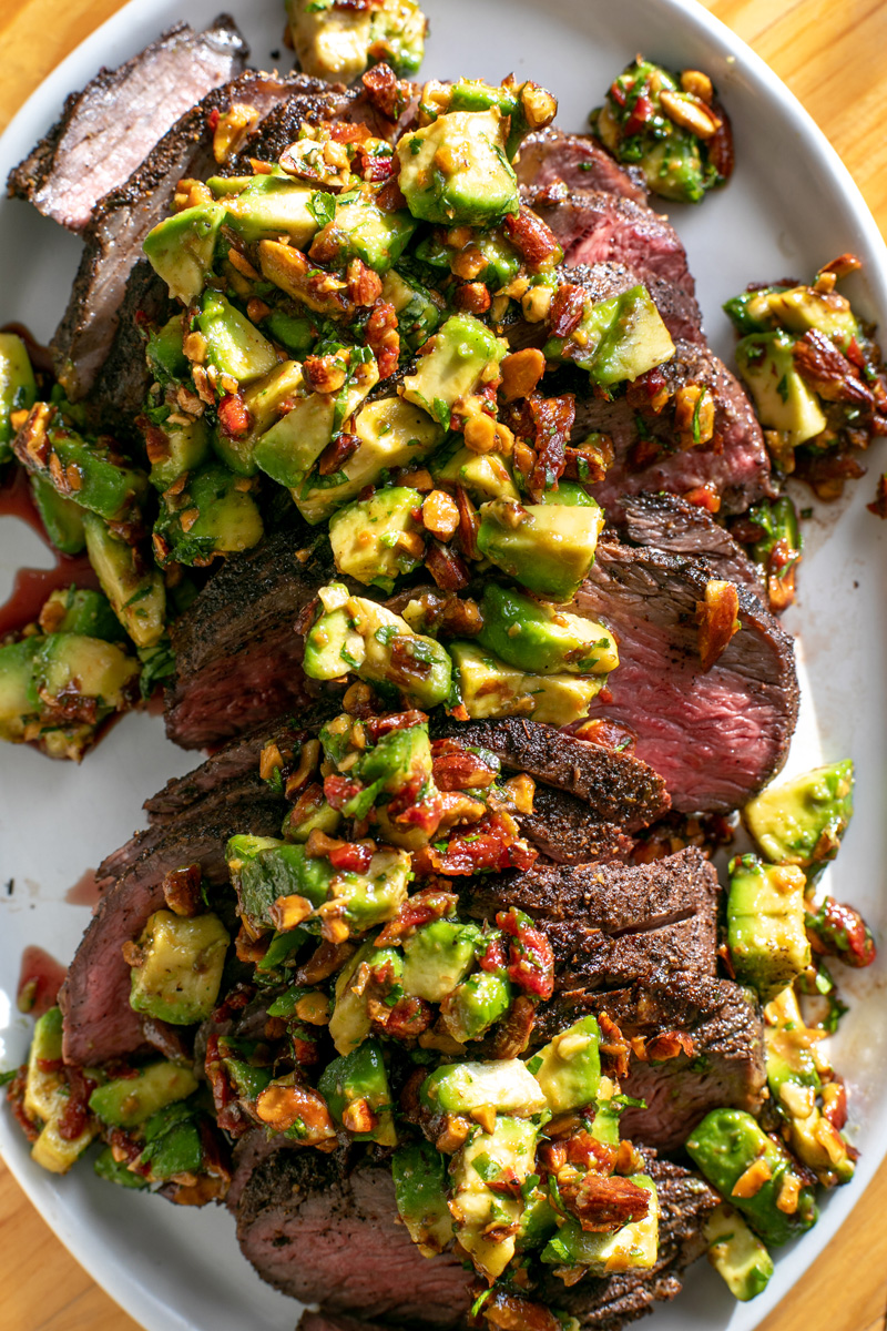 a close up image of a grilled tri-tip steak, cut into slices laying on an oval plate. On top of the steak is a vibrant avocado relish, that has pieces of sundried tomato visible in it