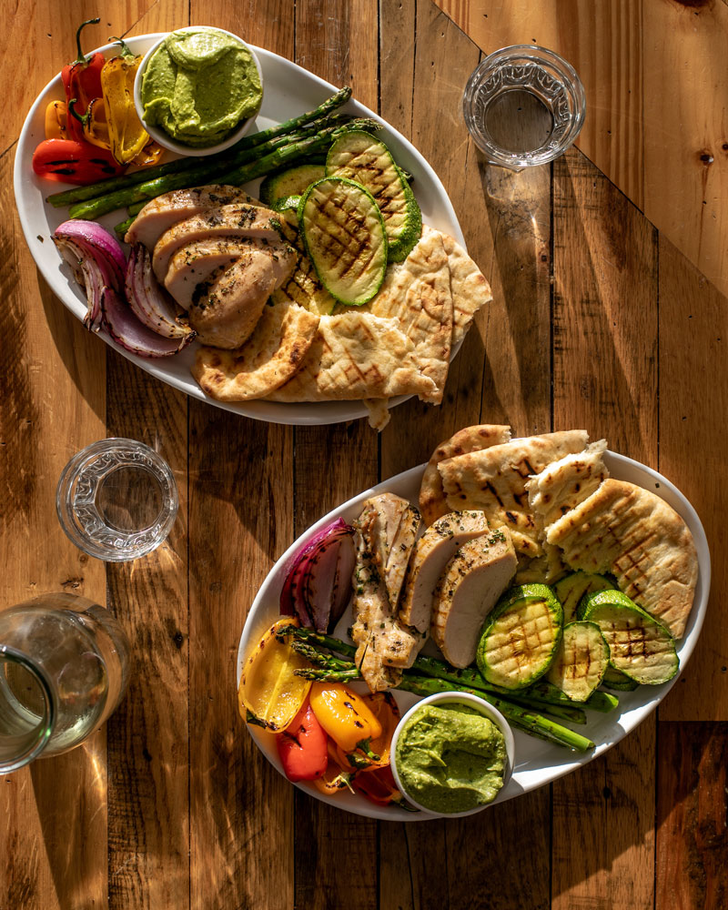 two oval platters on a wooden table, each platter has grilled vegetables, chicken, and flatbread on it along with a small ramekin of green avocado-feta dipping sauce