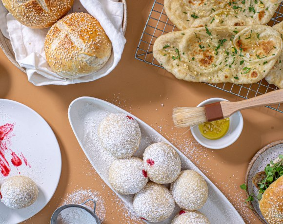 Overhead spread of things made out of pizza dough. In the top right is a wire rack with flatbread, next to it is a ramekin with garlic butter and a brush, below that is a hamburger with a sesame bun. In the middle is a long oval plate with powdered-sugar dusted jelly donuts, in the bottom left corner is a white plate with three jelly donuts, and in the top left corner is a basket of sesame buns.