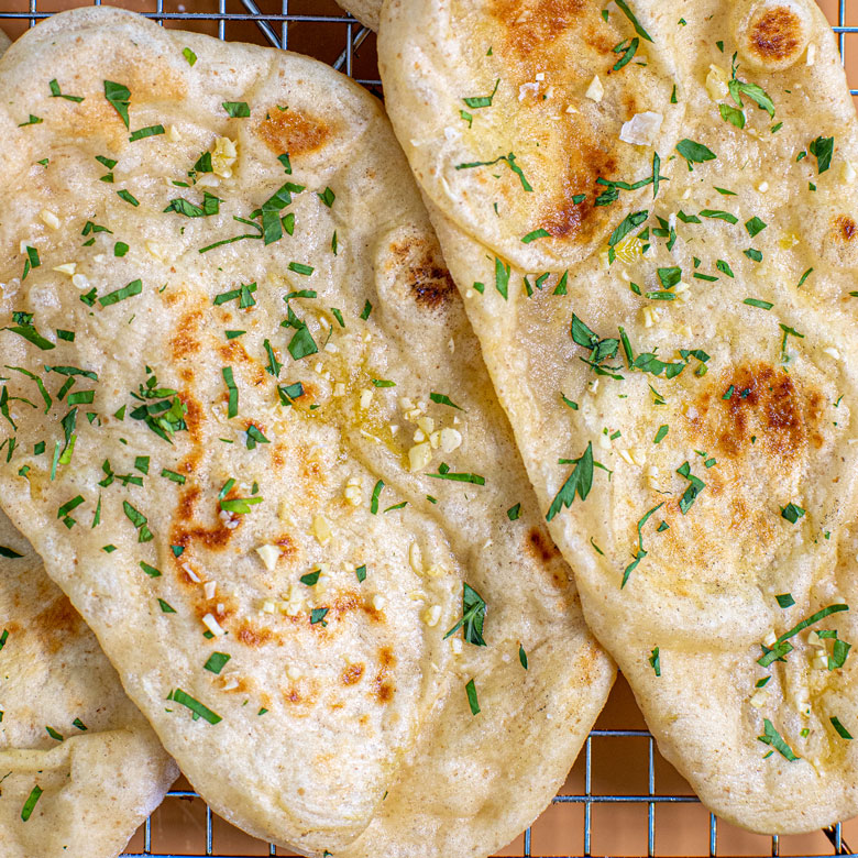 a close up of naan-style flatbreads on a wire rack, sprinkled with garlic butter, chopped parsley, and sea salt