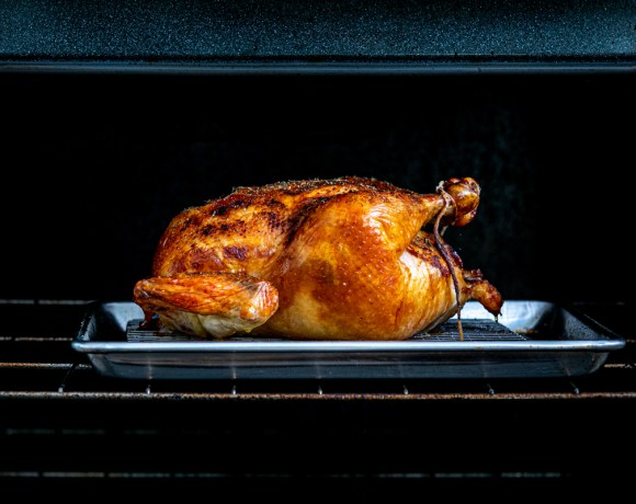 a golden roasted chicken sits on a sheet tray in an open oven
