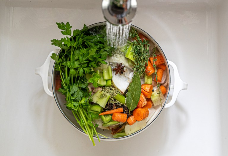 overhead view of a stock pot, filled with vegetables, herbs, chicken and spices, is being filled with water